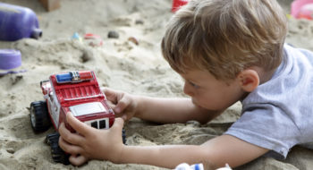 Child playing with toy car in a sandbox
